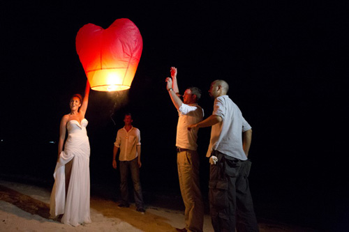 Wedding guests releasing Chinese lanterns on beach