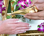 Thai wedding guests pour holy water on the hands of the married couple.